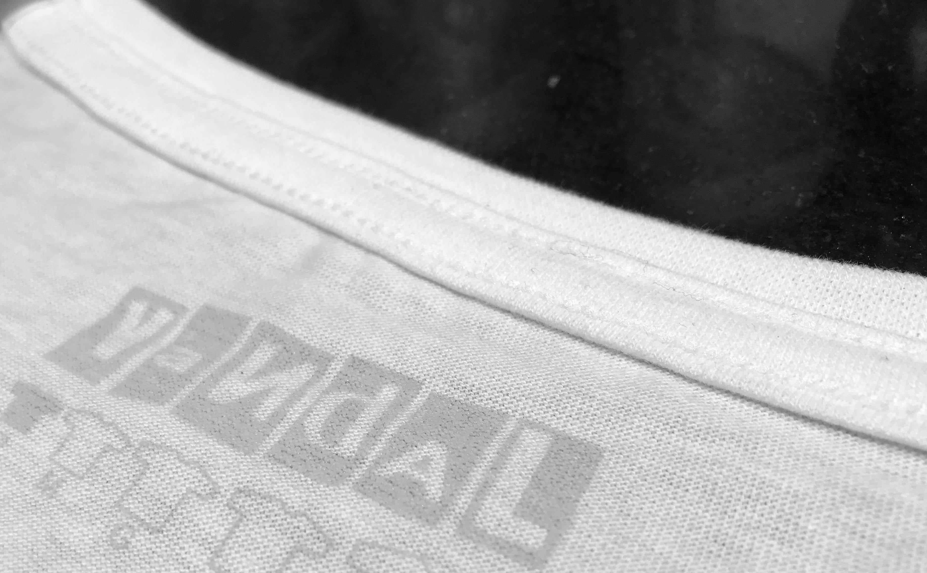 Zoom mostrando a qualidade da costura na gola de uma camiseta